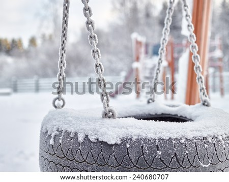 Close up, snowy playground in December, frost and cold weather - stock photo