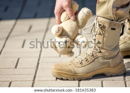 Close-up soldier with a toy, fluffy bear. concept - stock photo