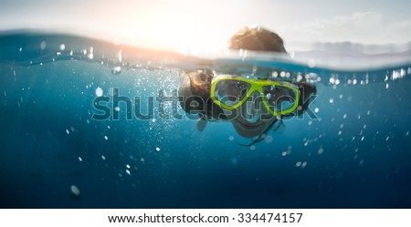 Close up split shot of the young lady snorkeling in the clear tropical sea - stock photo