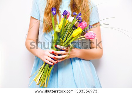 Close up spring fashion details, blonde woman holding beautiful bouquet of colorful tulips, wearing stylish pastel blue dress, white background, spring is coming. - stock photo