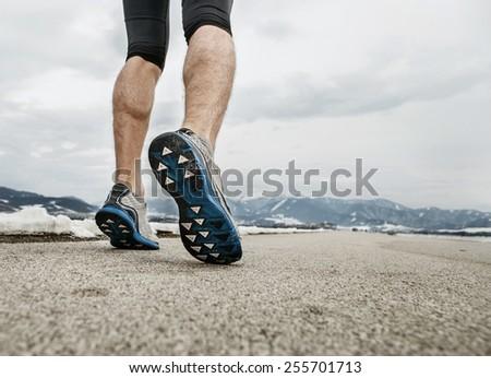 Close up sprinter legs on asphalt - stock photo