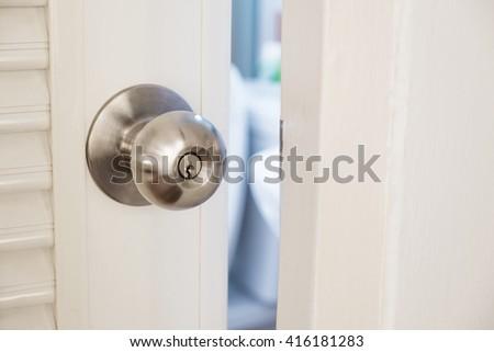 Close-up stainless door knob, with door open slightly - stock photo