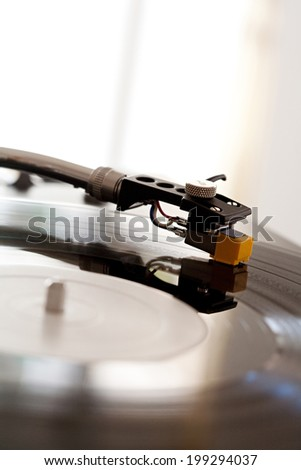 Close up still life detail view of a DJ record player needle touching the groove of the album, playing music against a bright window in a music club, interior. Musical hobbies and interests. - stock photo