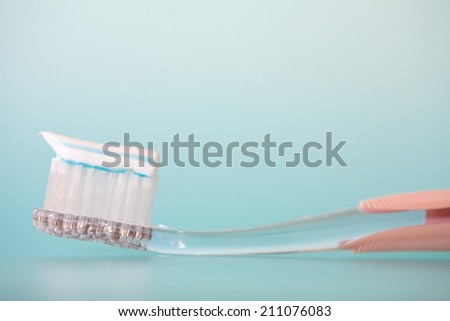 Close up still life detail view of refreshing stripy toothpaste on a new toothbrush, laying isolated on a spacious clean blue background, home bathroom interior. - stock photo
