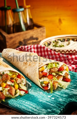 Close Up Still Life of Chicken Fajitas Stuffed with Fresh Vegetables and Resting on Worn Blue Cutting Board on Table with Condiments and Dressings in the Background - Tex Mex Mexican Meal - stock photo