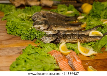 Close Up Still Life of Oily Smoked Whole Fish Arranged on Wooden Board with Green Lettuce Leaf and Lemon Wedge Garnish with Copy Space - stock photo