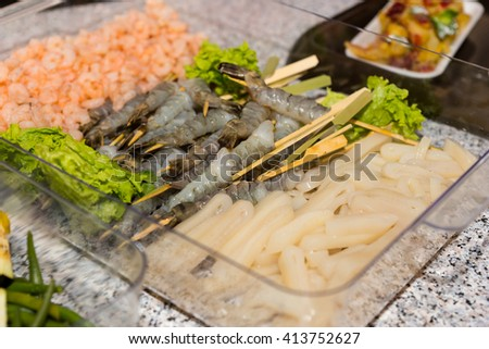 Close Up Still Life of Raw Prepared Fish, Shrimp and Seafood in Plastic Tray Ready for Grilling at Self Serve Restaurant Banquet Buffet - stock photo