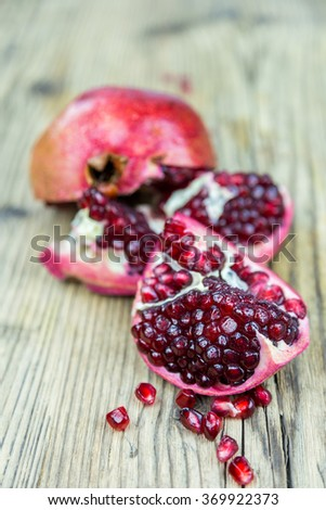 Close Up Still Life of Ripe Pomegranate Split on Wooden Table Surface with Juicy Red Seeds and Whole Fruit in Background - stock photo