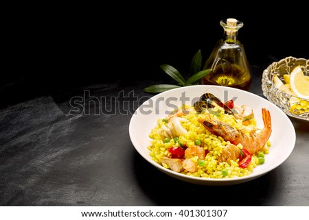 Close Up Still Life of Traditional Spanish Paella Dish Made with Yellow Saffron Rice and Fresh Seafood and Shellfish Served in White Bowl with Lemon and Olive Oil on Dark Surface with Copy Space - stock photo