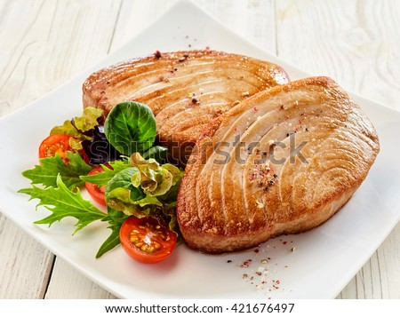 Close Up Still Life of Two Fried Tuna Steaks on Square White Plate with Seasoning and Fresh Green Salad with Tomato on Painted Wooden Table - stock photo