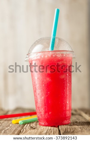 Close Up Still Life Profile View of Refreshing Frozen Red Slush Drink Served on Rustic Wooden Table with Colorful Drinking Straws - stock photo