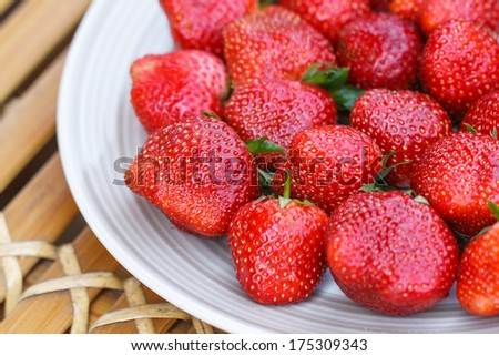 Close-up strawberry in a disk on bamboo table - stock photo