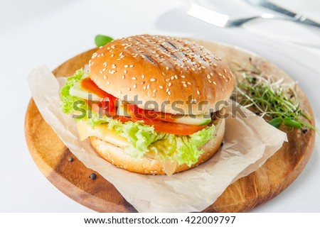 Close up Street Fast food  burger with grilled chicken fillet, cheese and vegetables  on the wooden board on served restaurant table. Highlight, selective focus - stock photo