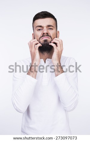 Close-up studio portrait of a man irritable itchy his beard and wants to shave it. Isolated on a light background. - stock photo