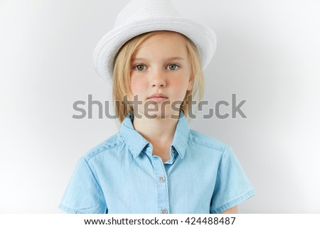 Close up studio portrait of beautiful Caucasian little girl with long blonde hair wearing white hat and denim shirt looking with serious expression at the camera. People and lifestyle concept.  - stock photo