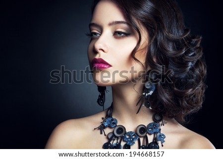 Close-up studio portrait of beautiful woman. Beautiful brunette model with long curly brown hair. - stock photo