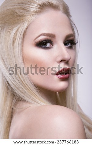 Close-up studio portrait of beautiful woman with dark make-up - stock photo