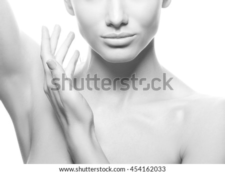 Close-up studio portrait of beautiful young caucasian brunette woman with natural lips and make-up isolated on white. Naked shoulders. Touch her perfect skin. Black and white - stock photo