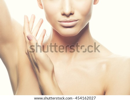 Close-up studio portrait of beautiful young caucasian brunette woman with natural lips, make-up and blue eyes isolated on white. Touch her perfect skin. Studio portrait. Toned - stock photo
