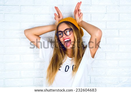 Close up studio portrait of cheerful blonde hipster girl going crazy making funny face and showing her tongue. White urban wall background.  - stock photo