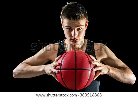 Close up studio portrait of handsome young basketball player holding inflated orange ball.Isolated against black background. - stock photo