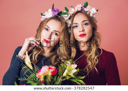 Close up studio portrait of two young pretty blonde women in spring  flowers wrath , amazing wavy long hairstyle , bright make up, looking at camera.   - stock photo