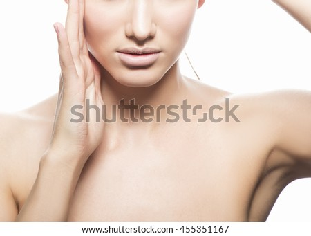 Close-up studio portrait of young caucasian brunette woman with natural lips, make-up and blue eyes isolated on white. Touch her head. Perfect skin. - stock photo