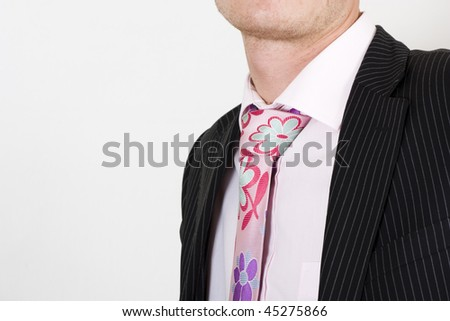Close up studio shot of a business man with a pink tie and black pinstripe suit, isolated on a white background. - stock photo