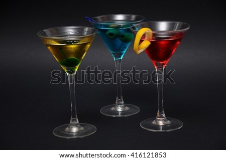 Close-up studio shot of a group of three garnished Martini cocktails (red, blue and yellow) on black background. - stock photo