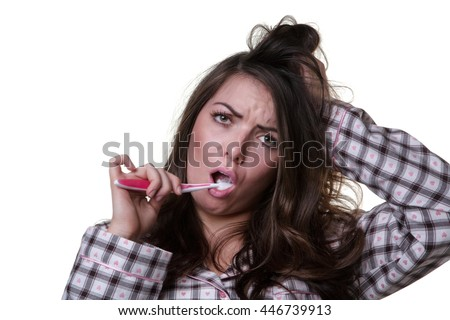 Close up studio shot of a sleepy looking model wearing her pyjamas and a toothbrush.  Isoalted on white background. - stock photo