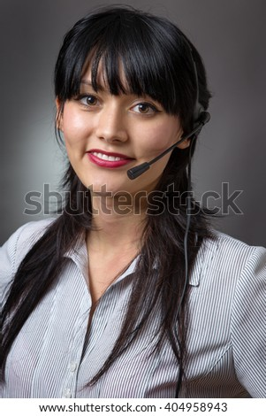 Close up studio shot of an attractive female call center operator, client services assistant or telemarketer wearing a headset looking at the camera with a charming friendly smile - stock photo
