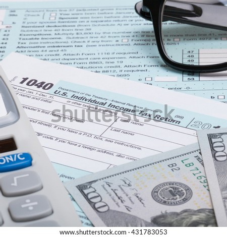 Close up studio shot of calculator, glasses and dollars over US 1040 Tax Form - stock photo