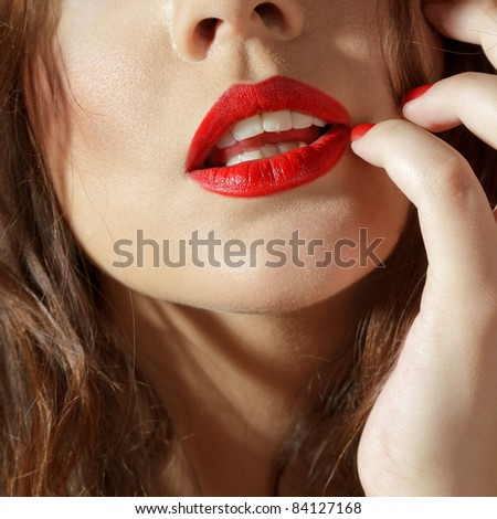 Close-up studio shot of female lips with fingers touching - stock photo