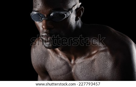 Close-up studio shot of young male swimmer training hard for swimming competition. Athlete with muscular body on black background. - stock photo