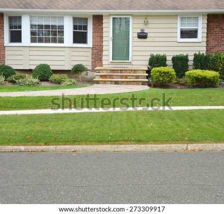 Close up Suburban Ranch Style home with Bay Window Green Door Brownstone Steps residential neighborhood USA - stock photo