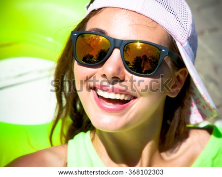 Close up summer portrait of a young girl hipster beautiful brunette teenage girl in sunglasses  having fun at pool party.Happy summer vacation girl. Beautiful caucasian woman having fun and smiling - stock photo