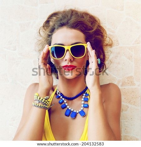 Close up summer portrait of young beautiful woman with bright make up posing outdoor in sunny day, wearing stylish neon bikini and sunglasses. - stock photo