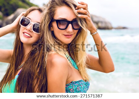Close up summer vacation portrait of blonde and brunette best friends girls, posing on the beach, wearing bikini and sunglasses, positive mood. - stock photo