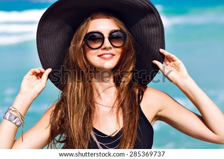 Close up sunny fashion portrait of pretty young brunette woman wearing big vintage elegant hat and young sunglasses, enjoy sunny day near blue ocean, vacation time, joy, happiness. - stock photo