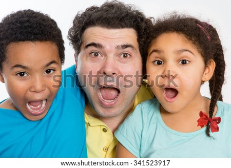 Close up Surprised Dad with Two Cute Kids Looking at the Camera with Mouth Wide Open Against White Background, Emphasizing Multicultural Family. - stock photo