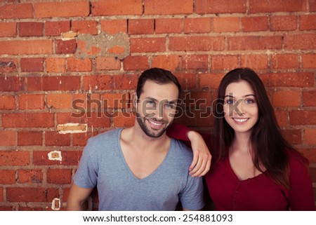 Close up Sweet Young Couple Posing In Front Brick Wall While Looking at the Camera. - stock photo