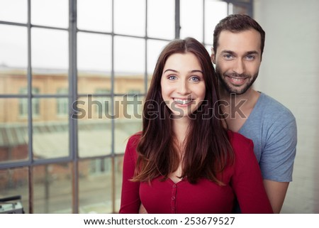 Close up Sweet Young Lovers in Casual Clothing Smiling at the Camera While Standing Near the Glass Window. - stock photo