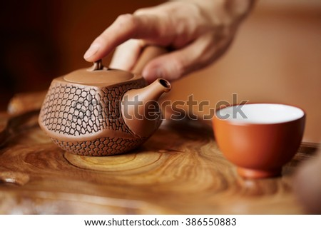 Close up table for traditional tea ceremony utensils, Chinese teacup and hand of tea master background at home - stock photo