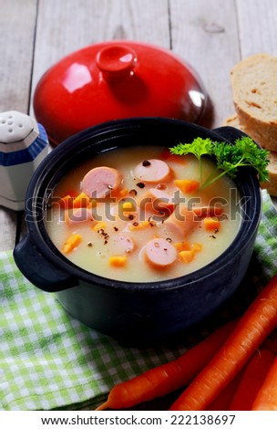 Close up Tasty Healthy Creamy Soup with Sausage on Black Pot Placed on Wooden Table. - stock photo