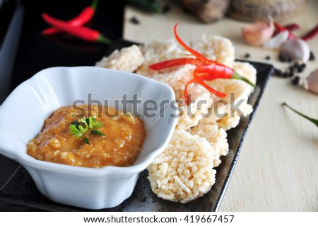 Close up Thai dip sauce with rice cracker on background - stock photo