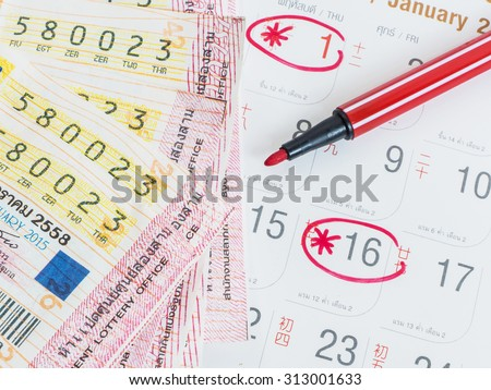 Close up Thai lottery tickets and Thai calendars with red marked of check out lottery date. - stock photo