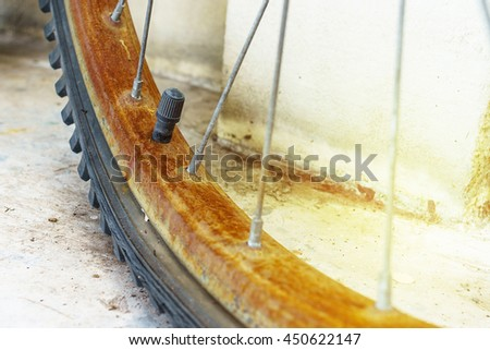 Close up the rust bicycle wheel and flat tyre, vintage retro style bicycle. election Focus on Tyre Valve Stem. - stock photo