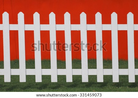 Close up the white wooden fence with green meadow and red wall background. - stock photo