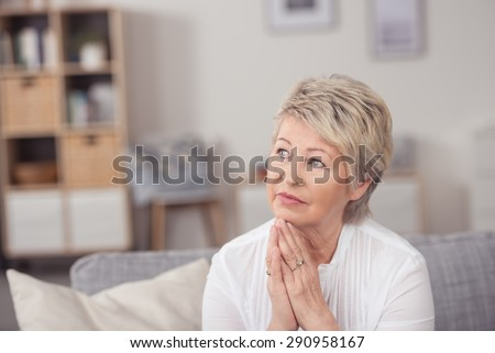 Close up Thoughtful Middle Aged Blond Woman, Sitting at the Living Room and Looking Up with Hands on the Chin. - stock photo