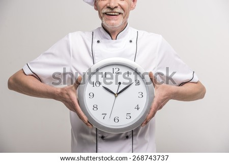 Close-up. Time to dinner. Senior male chief cook in uniform holding a clock on grey background. - stock photo
